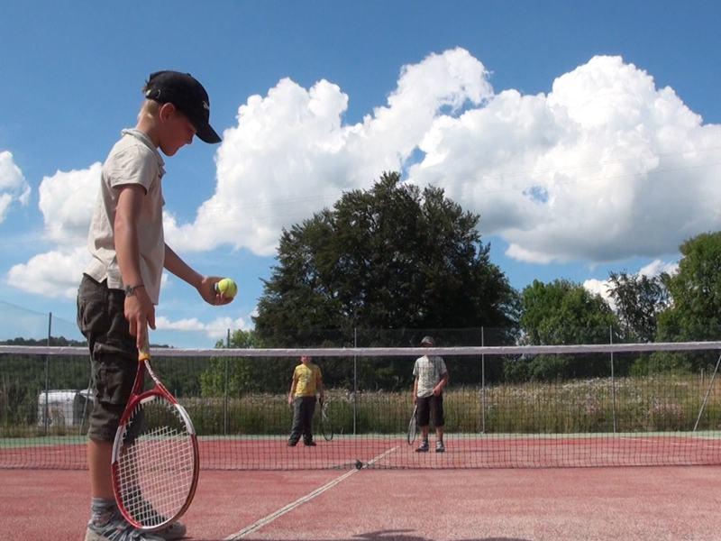 Enfant faisant un service au tennis en colonie de vacances cet été