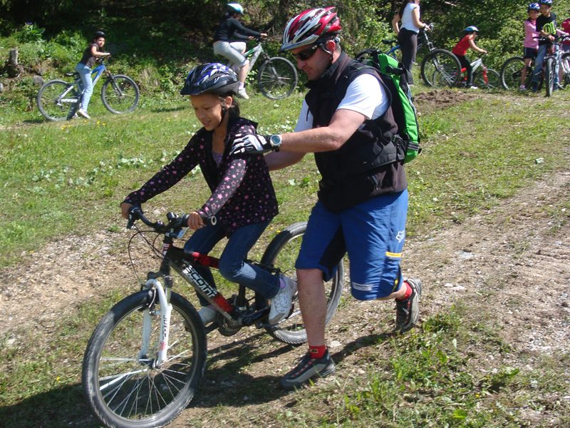 Enfant apprenant à faire du vélo en colonie de vacances cet été