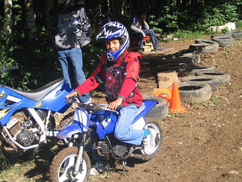 Enfant sur un terrain de motocross conduisant une moto en colo