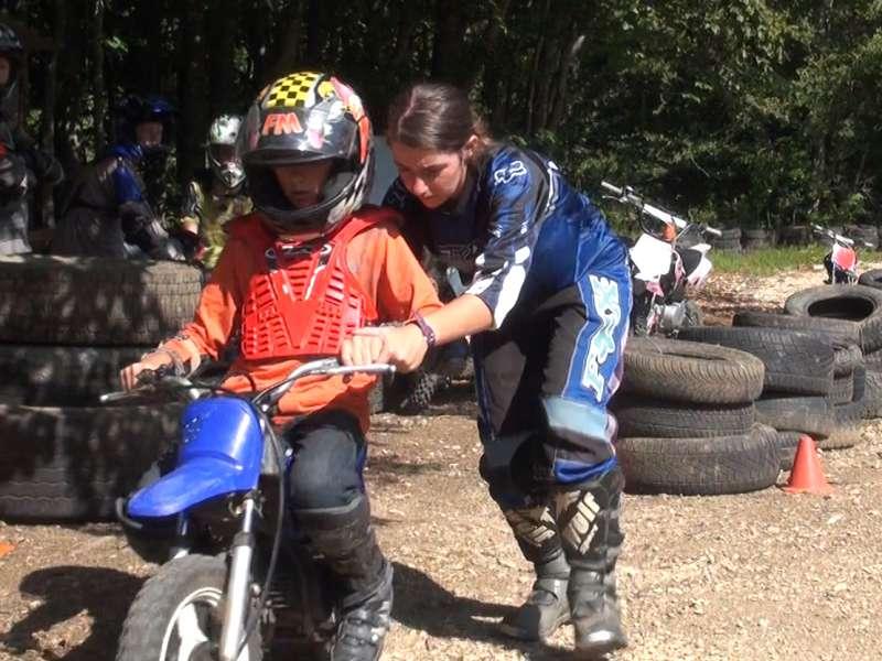 Monitrice apprenant à un enfant en colo à faire de la moto cross