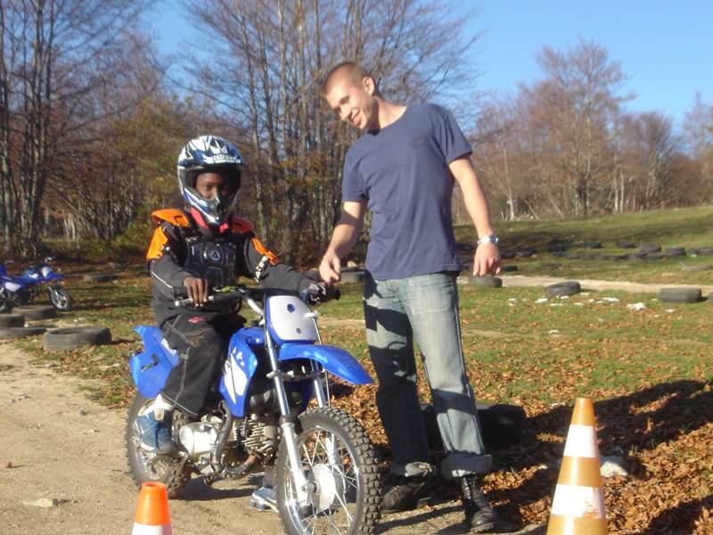 Ado apprenant à conduire une moto avec l'aide son animateur de colo