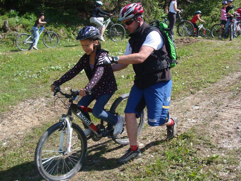Animateur de colonie de vacances aidant une jeune fille à faire du vélo