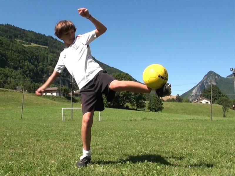 Garçon jouant au football en colonie de vacances été