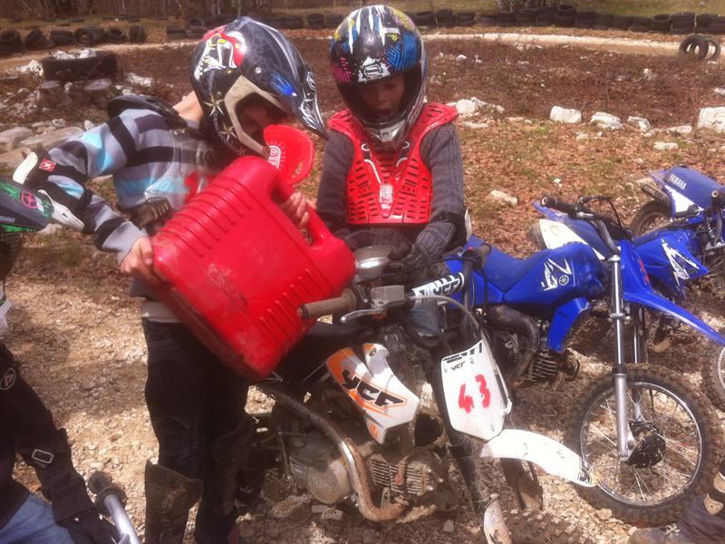 Enfants mettant de l'essence dans leur moto en colonie de vacances d'&été