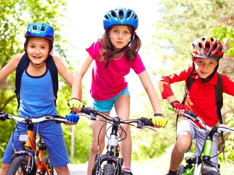 Trois enfants faisant du vélo à la campagne en colonie de vacances