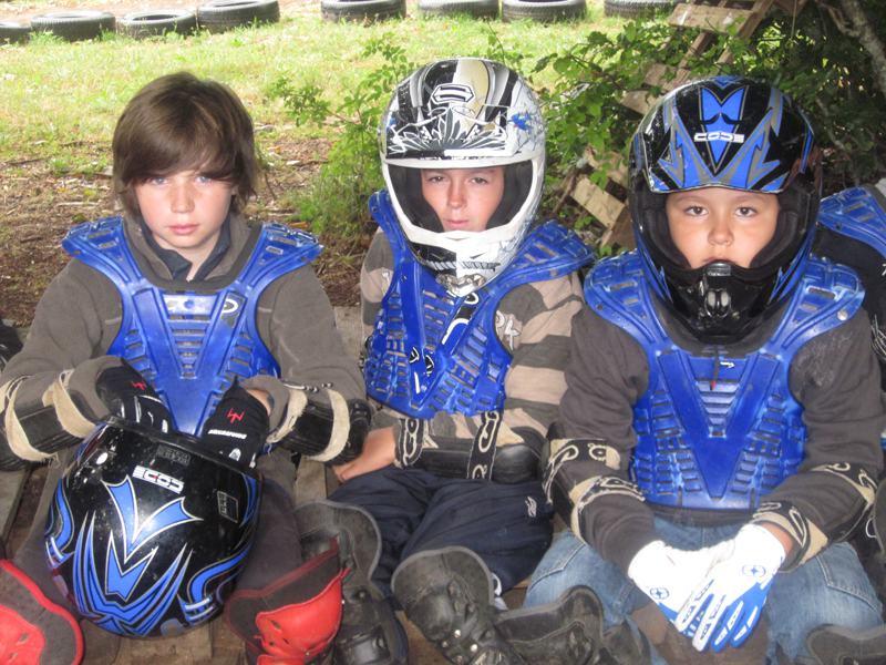 Trois enfants assis portant des équipements de moto en colo