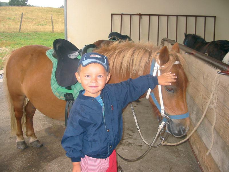 Petit garçon en colonie de vacances équitation été