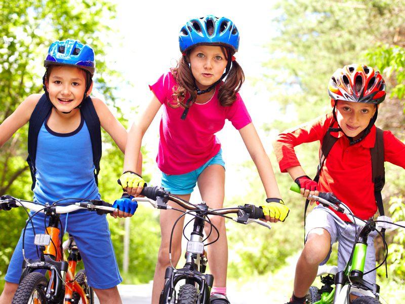 Trois enfants à vélo en colonie de vacances