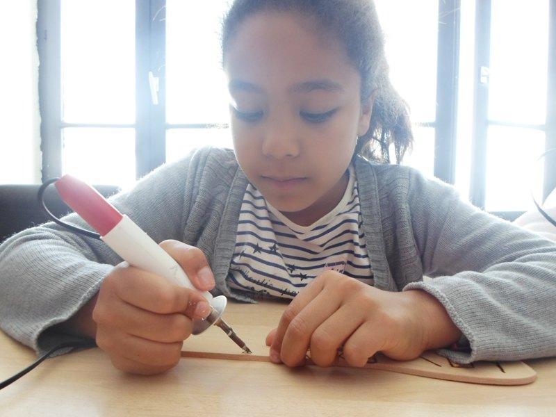 Fille de 10 ans faisant de la gravure sur bois en colo été