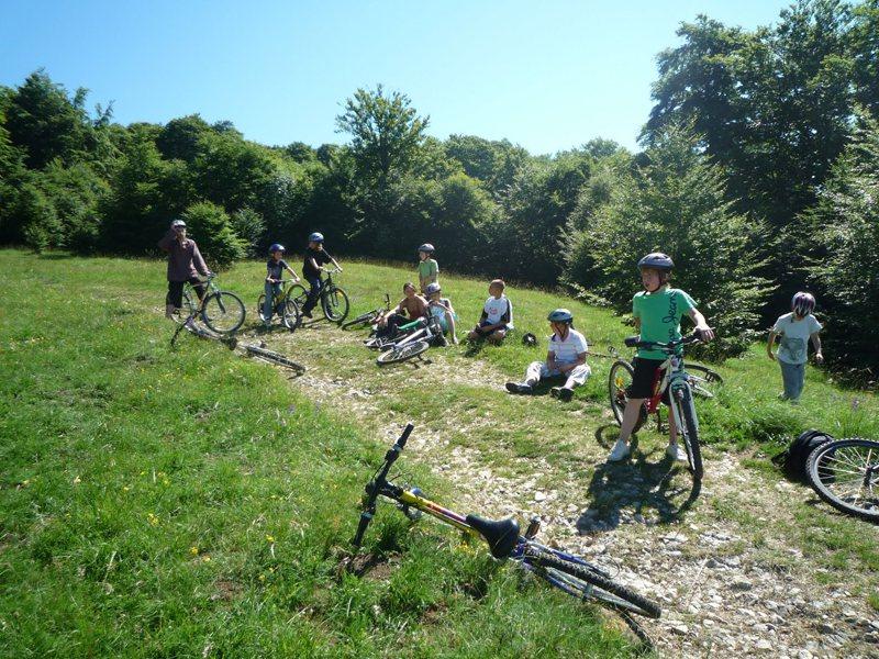Groupe d'enfants en randonnée à vélo en pleine nature en colo