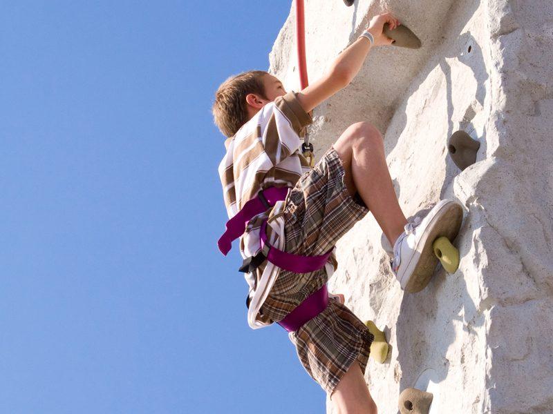 Enfant grimpant sur un mur d'escalade en colonie de vacances escalade été