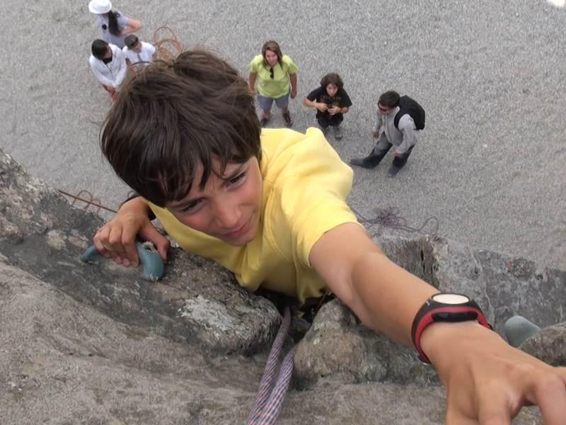Jeune garçon grimpant sur le mur d'escalade en colonie de vacances été