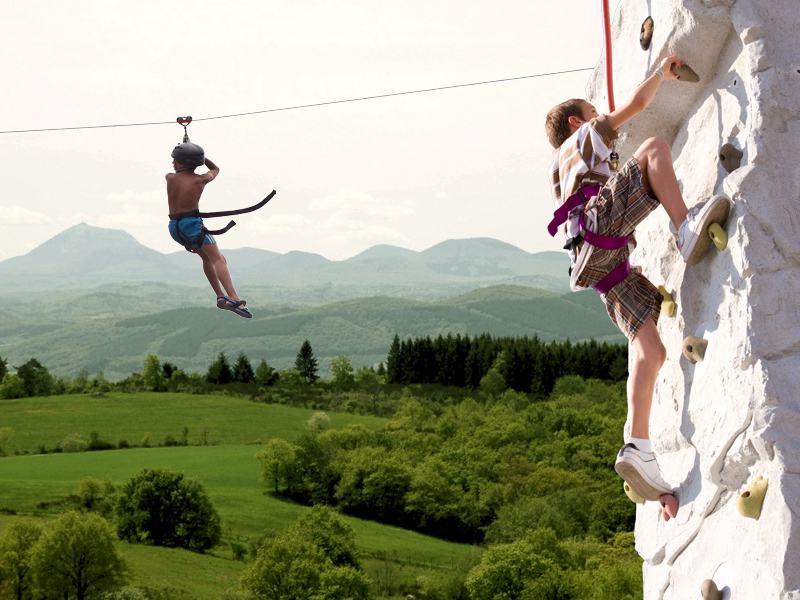 Jeunes garçons faisant de la tyrolienne et de l'escalade en colonie de vacances multiactivités cet été