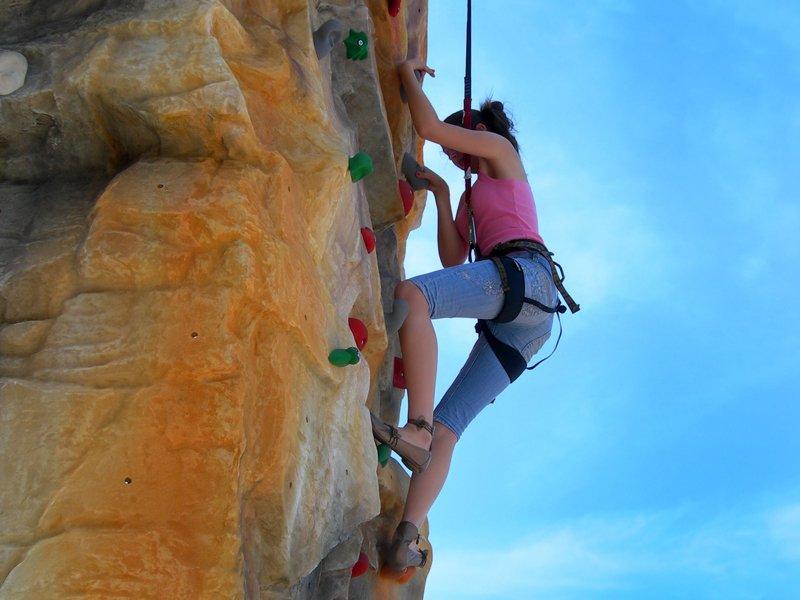Jeune fille pratiquant l'escalade en colonie de vacances d'été