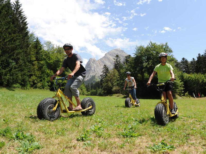 Groupe d'enfants sur des trottinettes tous terrains en colonie de vacances d'été