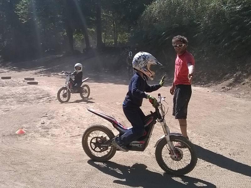 Deux enfants apprenant à faire de la moto en colonie de vacances cet été sous la surveillance du moniteur de colo