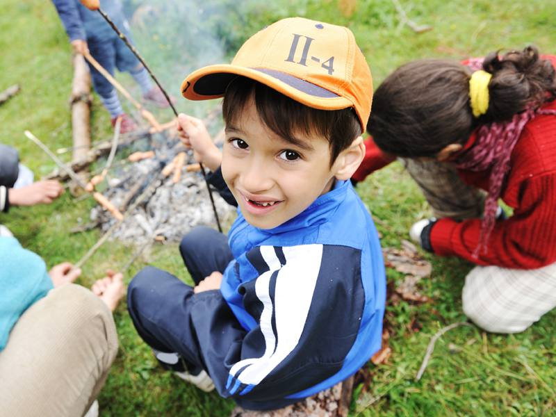 Enfant de 6 ans faisant griller un chamallow sur le feu en colonie de vacances été