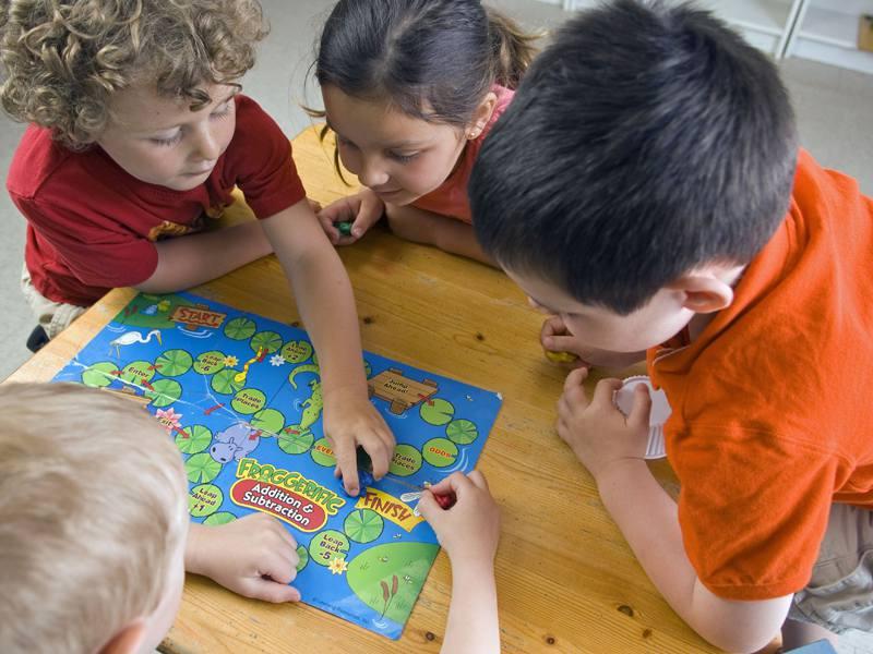 Jeunes enfants jouant à un jeu de société en colonie de vacances été