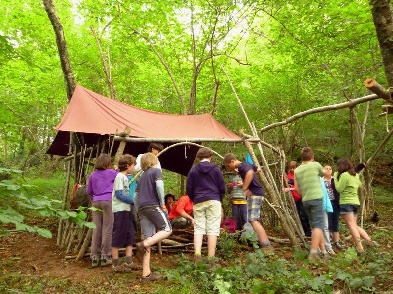 Groupe d'enfants en colonie de vacances construisant une cabane dans les bois été