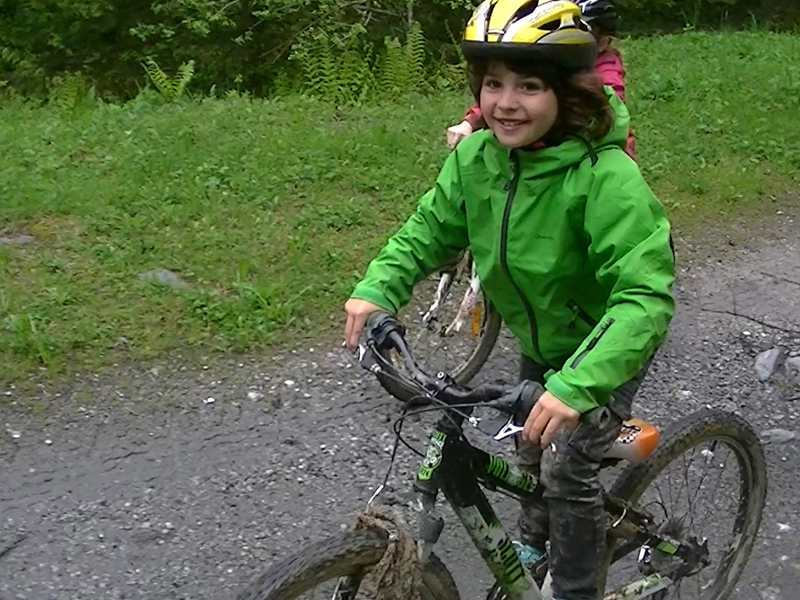 Jeune garçon heureux de faire du vélo à la campagne en colonie de vacances
