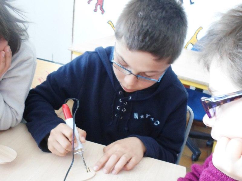 Enfant pratiquant la pyrogravure en colonie de vacances d'été