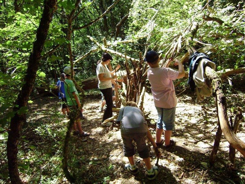 Groupe de jeunes enfants apprenant à construire une cabane en colonie de vacances été