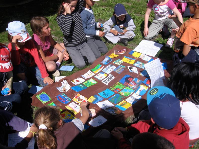 Enfants dehors jouant à un jeu de cartes fabriqué par leurs soins en colonie de vacances