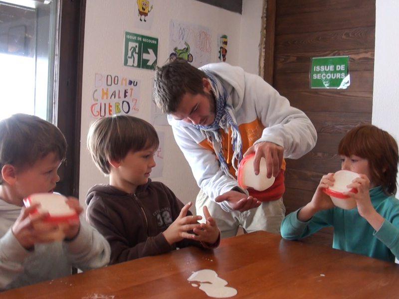 Enfants et leur animateur de colo apprenant à faire du fromage en colonie de vacances été
