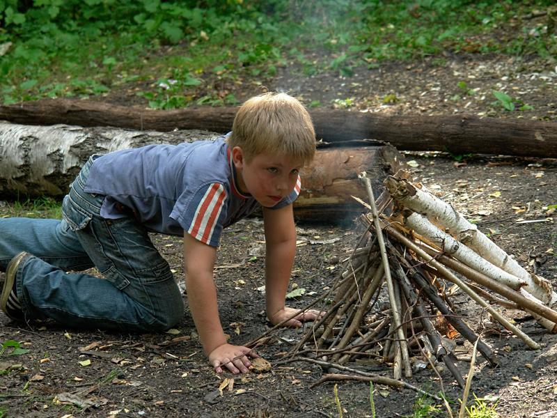 Garçonnet apprenant à faire du feu en colonie de vacances étér