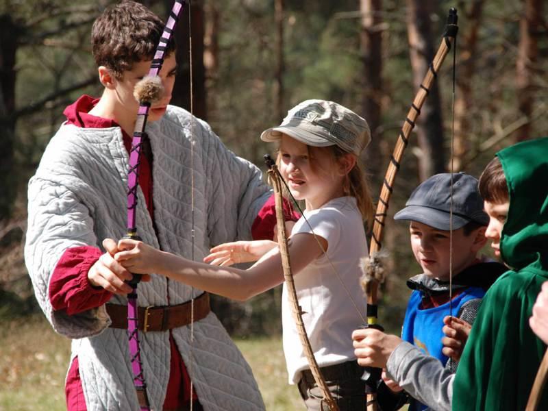 Fillette de 9 ans apprenant à tirer à l'arc sous la surveillance de l'animateur de colonie de vacances d'été