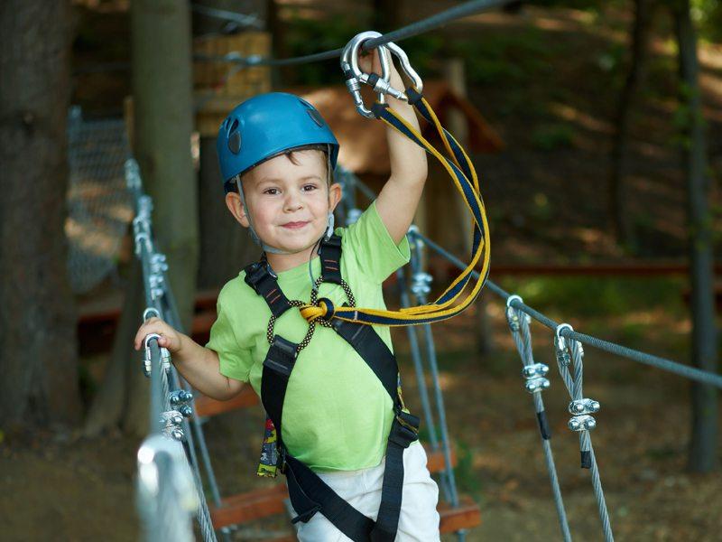 Petit garçon apprenant à faire de l'accrobranche en colonie de vacances d'été