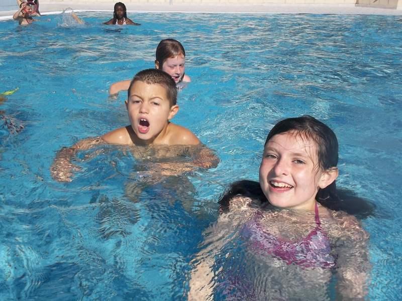 Enfants se baignant dans la piscine en colonie de vacances d'été