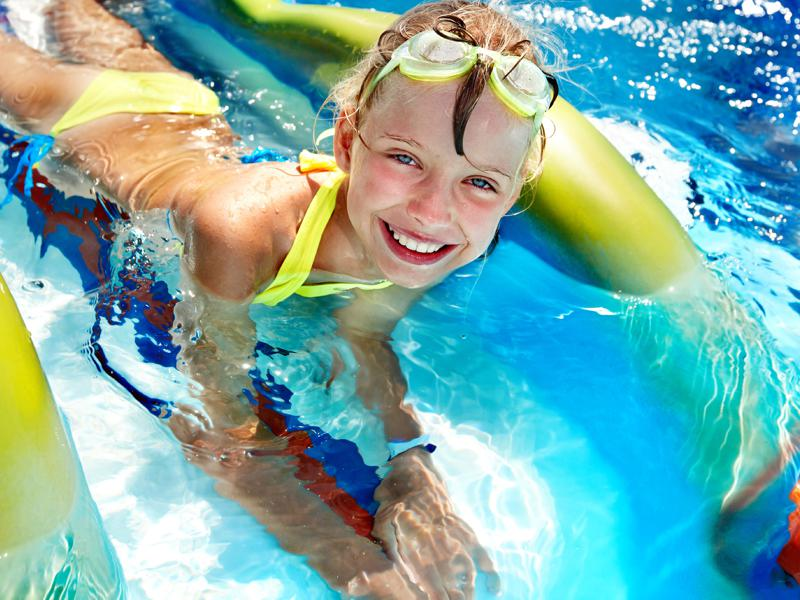 Fillette se baignant dans une piscine en colo été