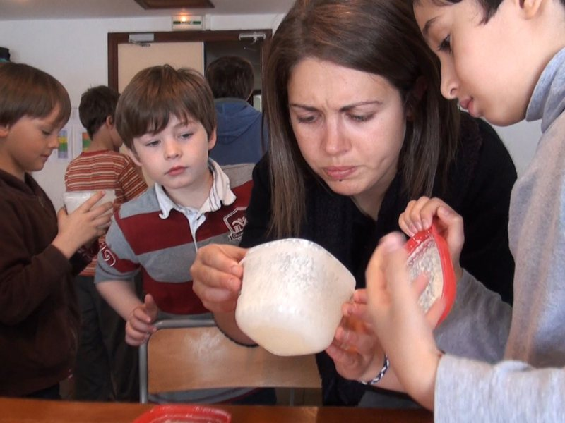 Animatrice de colonie de vacances montrant comment faire du fromage aux enfants en colo été