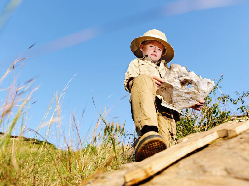 Enfant habillé en aventurier cherchant à se repérer grâce à une carte en colonie de vacances été
