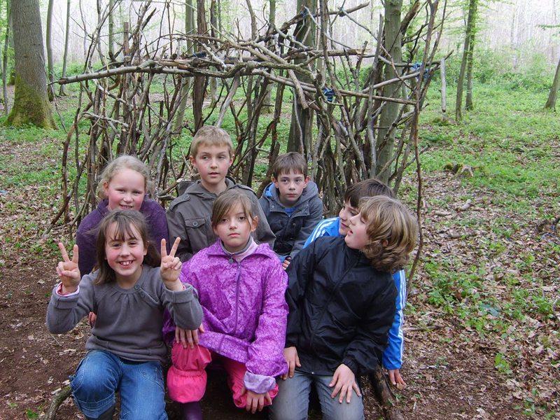Groupe d'enfants dans une cabane dans les bois en colonie de vacances été