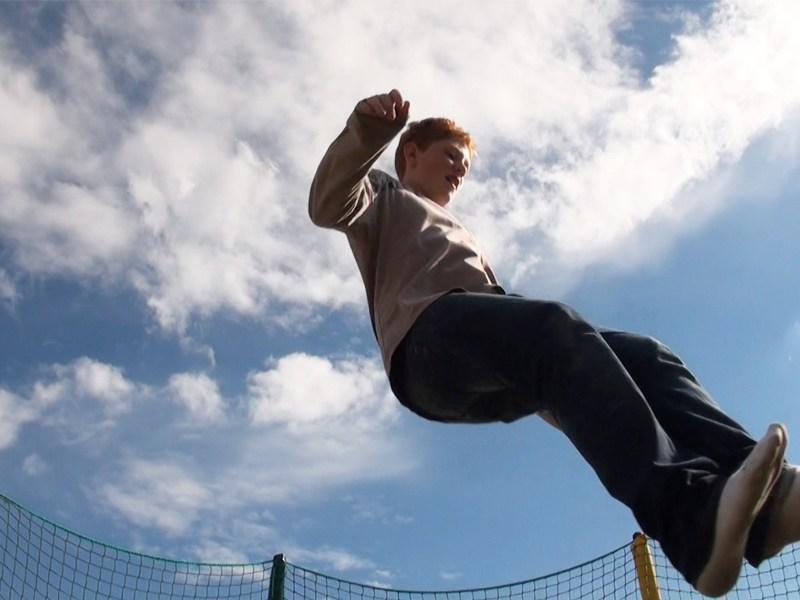 Ado sautant dans les airs en trampoline en colonie de vacances