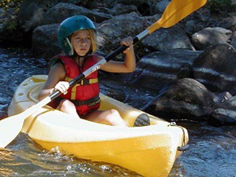 Enfant faisant du canoe kayak dans les rapides en colonie de vacances été