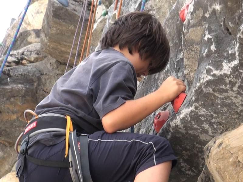 Enfant faisant de l'escalade sur voies naturelles en colo cet été