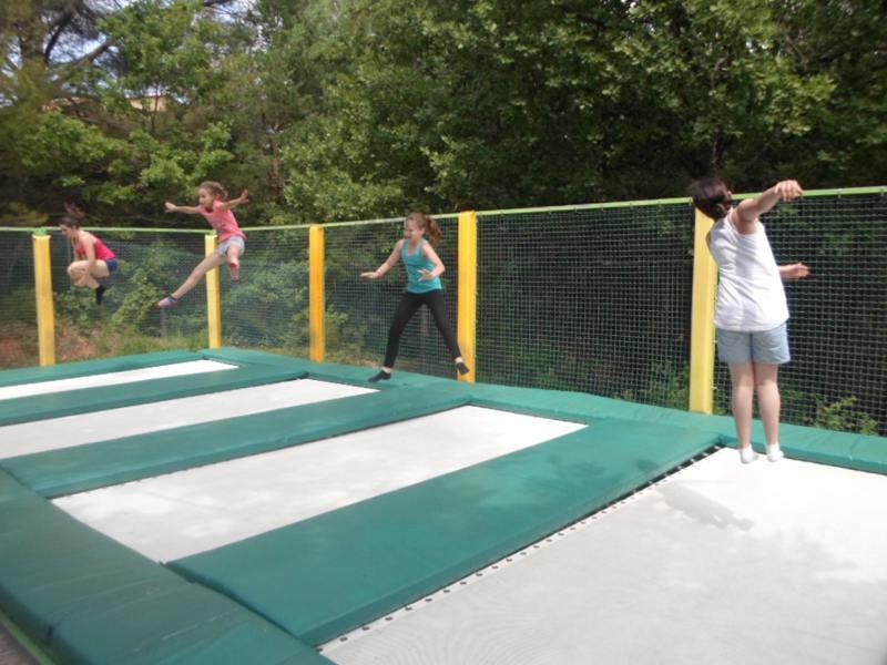 Quatre enfants faisant du trampoline en colonie de vacances trampoline été