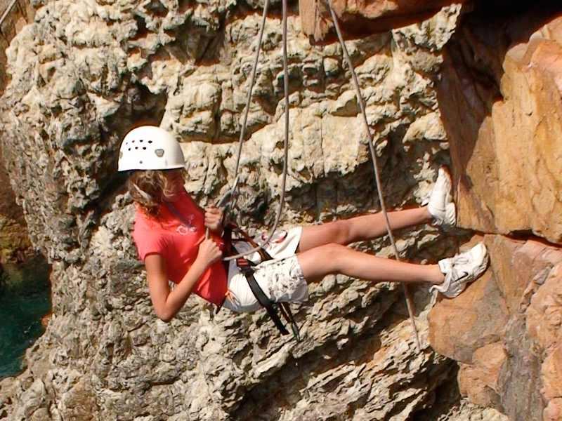 Jeune fille pratiquant la descente en rappel en colonie de vacances escalade été