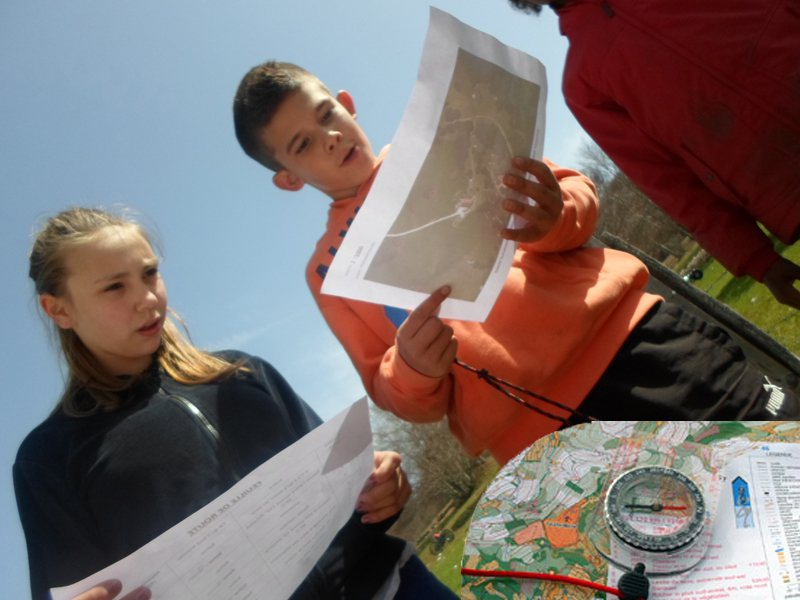 Deux enfants cherchant à se repérer avec une carte et une boussole en colonie de vacances