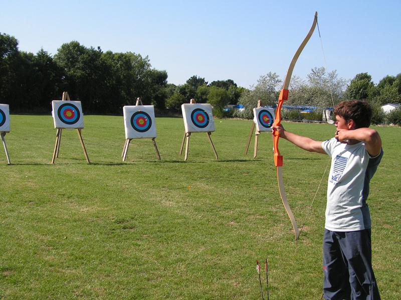 Enfant visant des cibles de tir à l'arc en colonie de vacances multi activités de sports été