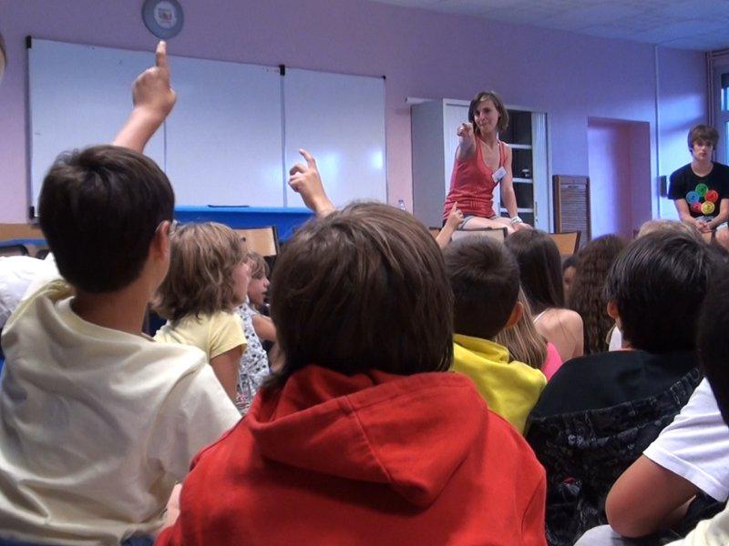 Enfants en colonie de vacances répondant aux questions de leur animatrice de colonie de vacances été