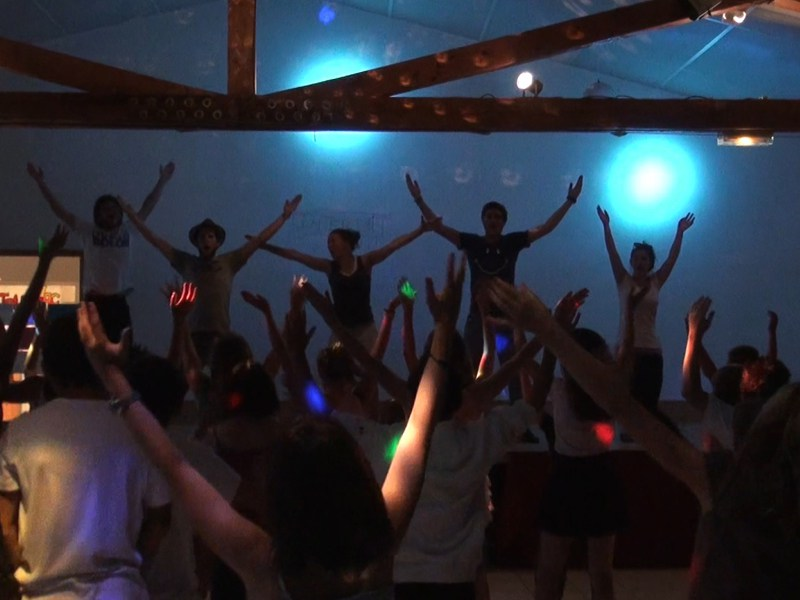 Groupe d'enfants en boom en colonie de vacances dansant avec leurs animateurs de colo été
