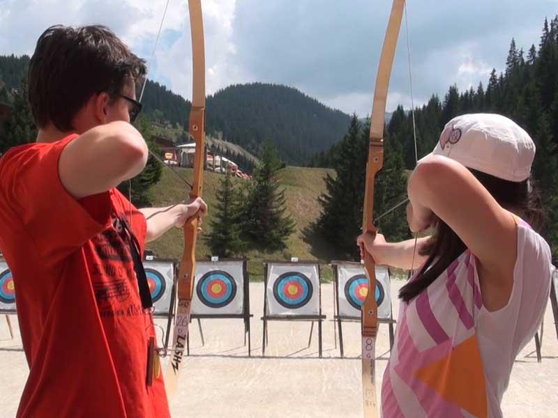 Deux adolescents visant les cibles avec leur arc en colonie de vacances tir à l'arc été