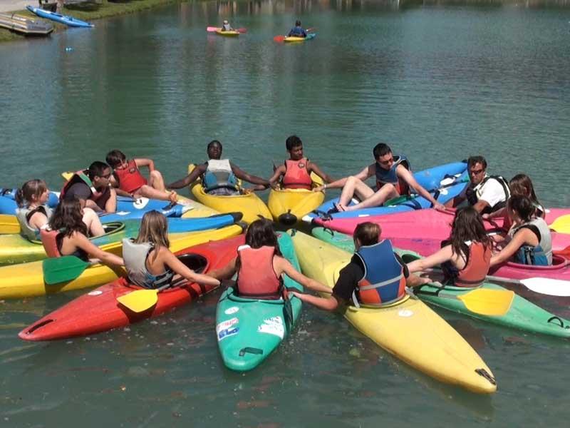 Enfants et leurs canoe kayak sur l'eau groupés ensemble en colonie de vacances été