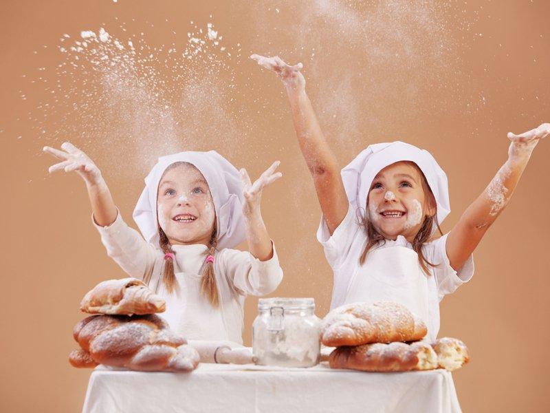 Deux fillettes avec une tenue de cuisine jettant de la farine en colonie de vacances cuisine été