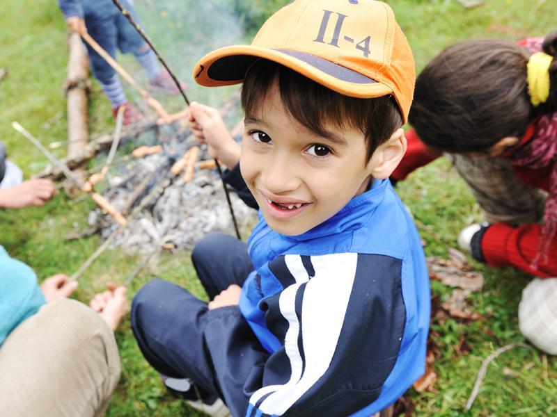 Petit garçon faisant griller un chamallow autour du feu en colonie de vacances