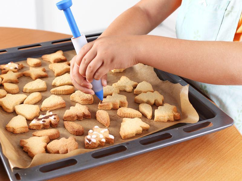 Main d'enfant décorant des biscuits en colonie de vacances cuisine été